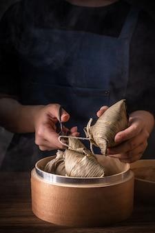 Zongzi, frau, die gedämpften reisknödel auf holztisch, berühmtes leckeres essen im drachenbootfestival duanwu designkonzept isst, nahaufnahme, kopienraum