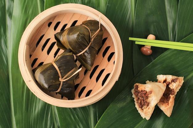 Zongzi oder bakcang, chinesische herzhafte klebreis-knödel in bambusblätter-verpackung. frisches konzept mit frischen bakcang-blättern.