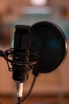 Zoomen auf professionelles mikrofon im vlogger-heimstudio und neonlicht im hintergrund. influencer, der social-media-inhalte mit produktionsmikrofon aufzeichnet. digitale web-internet-streaming-station