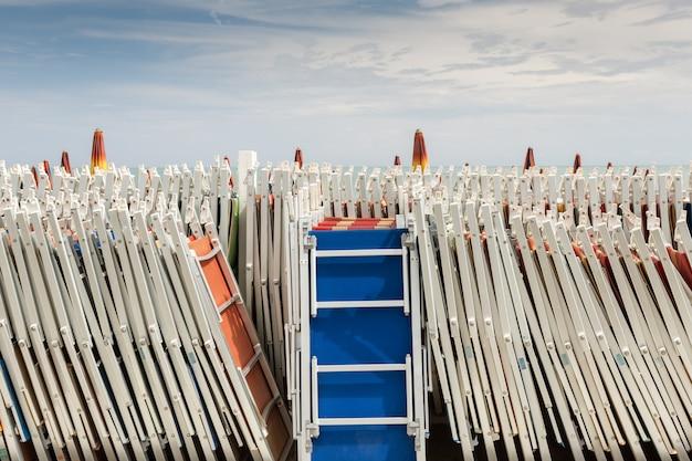 Zu beginn und am ende der badesaison sind die sonnenschirme geschlossen und warten auf ein paar tage warmen sonnenscheins.