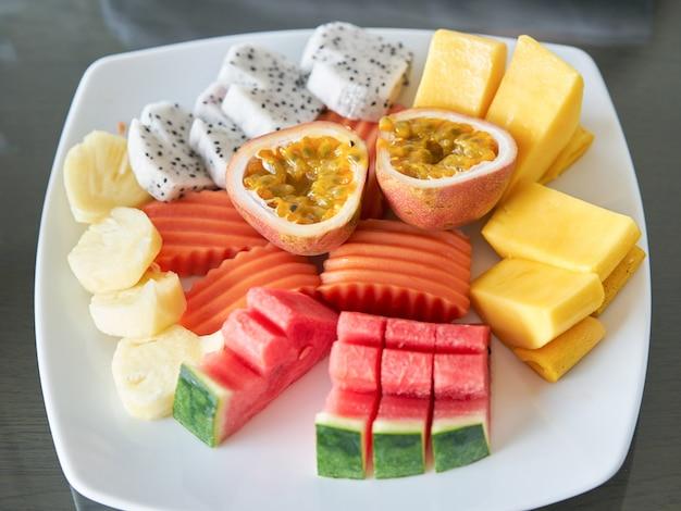 Zu den gemischten früchten gehören passionsfrucht, zerrissene mango, papaya, ananas, drachenfrucht und wassermelone auf einem teller zum nachtisch