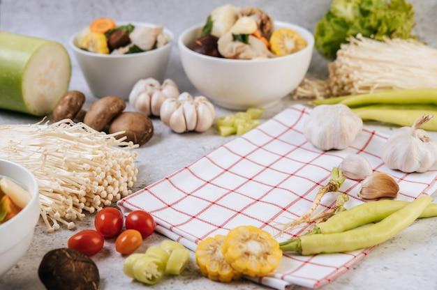 Zu den zutaten für die suppenherstellung gehören mais, shiitake-pilze, tomaten, nadelpilze, chili und knoblauch.
