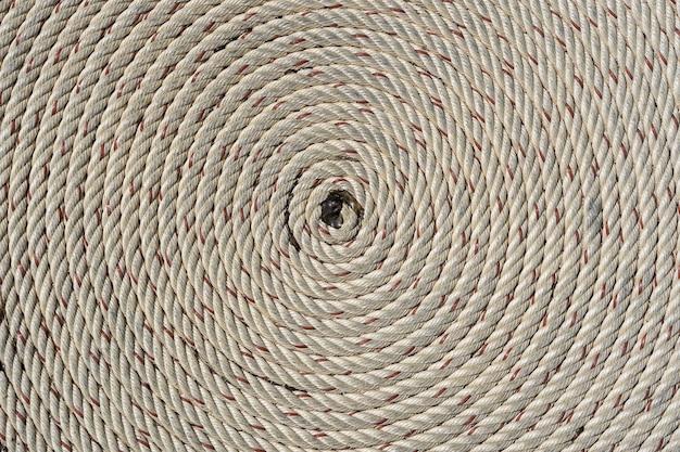 Zu einer spirale gefaltetes seil, nahaufnahme. verdrehter seilhintergrund