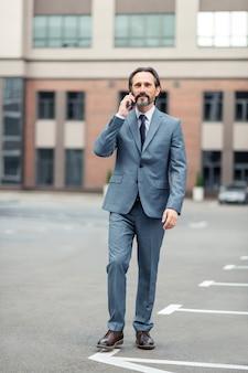 Zu fuß gehen. grauhaariger reifer mann im grauen anzug ruft kollegen an, während er zu fuß geht