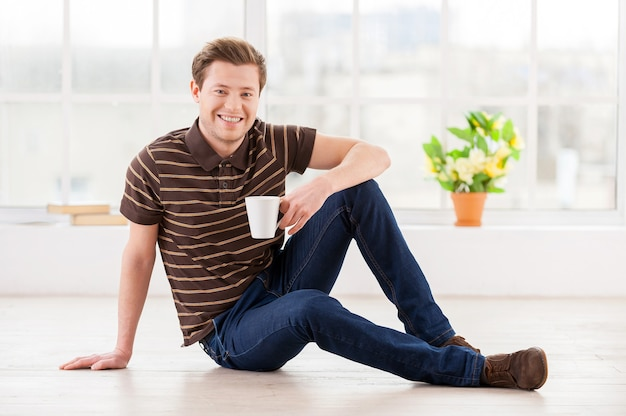 Zu hause entspannen. hübscher junger mann, der eine tasse hält und in die kamera lächelt, während er in seiner wohnung auf dem boden sitzt