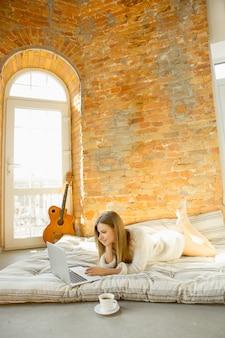 Zu hause entspannen. schöne junge frau, die auf matratze mit warmem sonnenlicht liegt.