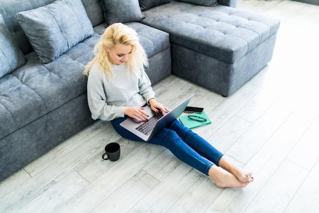 Zu hause entspannen. schöne junge frau, die ihren laptop benutzt, während zu hause auf teppich liegend