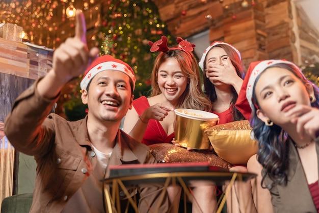 Zu hause entspannende und glückliche menschen, die mit popcorn-snack feiern und einen film schauen