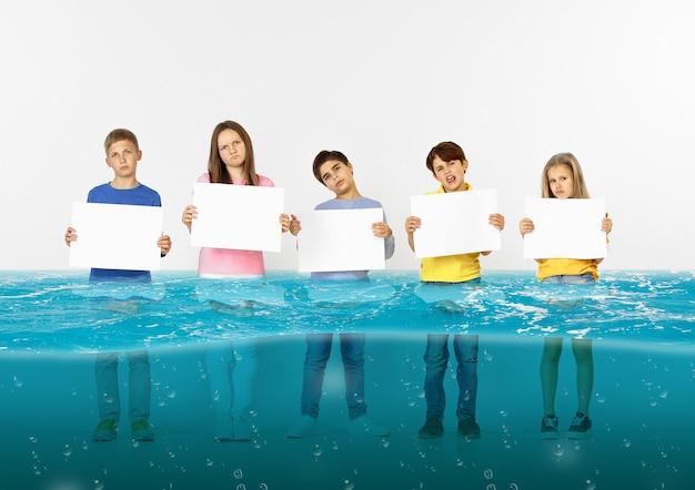Zu hause ertrunken. gruppe von kindern mit leeren bannern, die im wasser des schmelzenden gletschers stehen, globale erwärmung. ökologie, umweltkonzept. retten sie den planeten für die zukünftige generation, hören sie auf, die natur zu übernutzen.