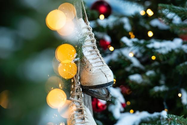 Zu hause hing ein paar schlittschuhe, verziert mit weihnachtsschmuck. defokussierter weihnachtsbaum im hintergrund