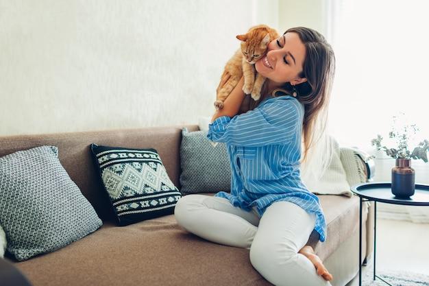 Zu hause mit der katze spielen. junge frau, die auf couch mit haustier sitzt.