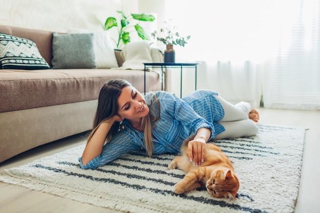 Zu hause mit der katze spielen. junge frau, die auf teppich liegt und haustier neckt.