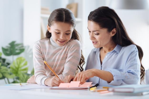 Zu hause studieren. erfreute positive kluge frau, die zusammen mit ihrer tochter sitzt und lächelt, während sie ihr beim lernen hilft