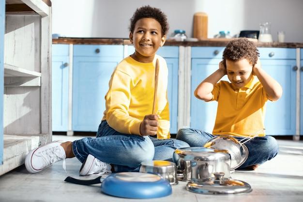 Zu laut. fröhliche kleine jungen sitzen auf dem küchenboden und erzeugen laute geräusche, indem sie auf töpfen trommeln, während einer der jungen seine ohren bedeckt