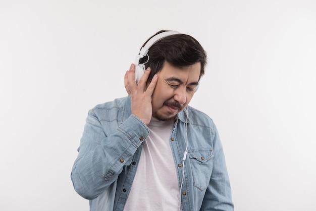 Zu laut. netter erwachsener mann, der kopfhörer trägt, während musik hört