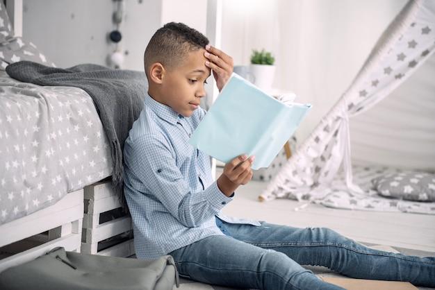 Zu schwer. ängstlicher afroamerikanischer junge, der gesicht beim lesen des buches berührt