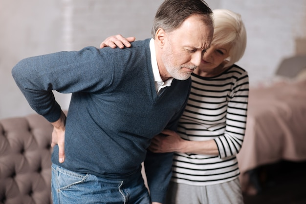 Zu stark. porträt eines alten mannes, der mit schrecklichen rückenschmerzen steht, während seine frau ihn unterstützt.
