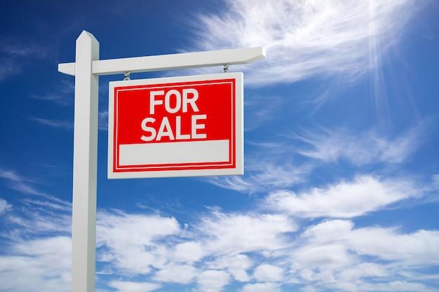 Zu verkaufen immobilien schild über wolken und blauer himmel. 3d-darstellung