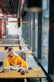 Zu viel arbeit junge geschäftsfrau, die einen gelben pullover trägt und sich überlastet fühlt, weil sie zu viel arbeit hat
