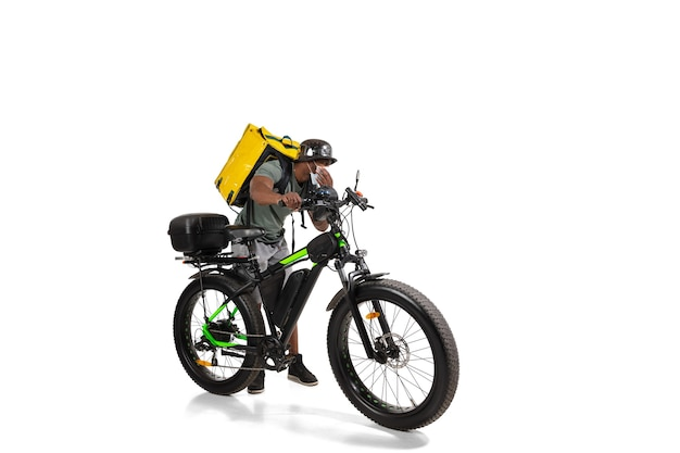 Zu viele bestellungen. kontaktloser lieferservice während der quarantäne. mann liefert essen während der isolation, trägt helm und gesichtsmaske. nahrungsaufnahme auf dem fahrrad isoliert auf weißer wand. sicherheit. sich beeilen.