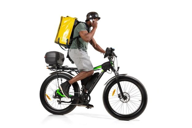Zu viele bestellungen. kontaktloser lieferservice während der quarantäne. mann liefert essen während der isolation, trägt helm und gesichtsmaske. nahrungsaufnahme auf dem fahrrad isoliert auf weißer wand. sicherheit. sich beeilen. Kostenlose Fotos