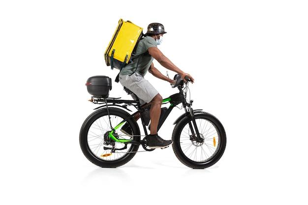 Zu viele bestellungen. kontaktloser lieferservice während der quarantäne. mann liefert während der isolation essen, trägt helm und gesichtsmaske. nahrungsaufnahme auf dem fahrrad isoliert auf weißer wand. sicherheit. sich beeilen.