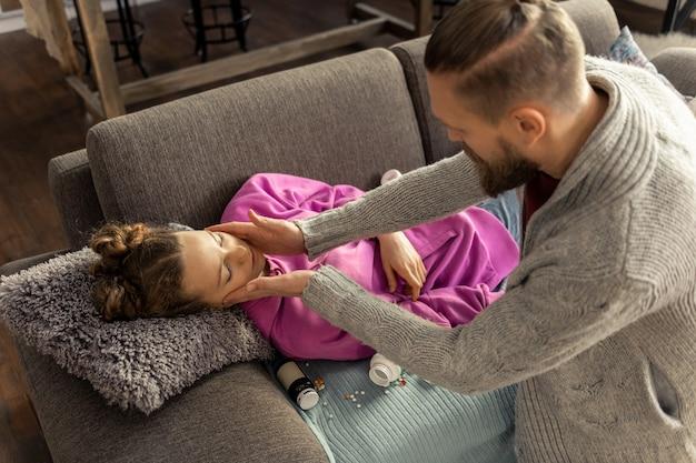 Zu viele pillen. vater sieht seine tochter auf dem sofa liegen und schlafen, nachdem er zu viele tabletten genommen hat taking