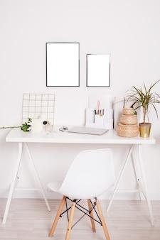 Zubehör auf regal neben weißem stuhl am schreibtisch mit laptop, pflanze und blumen im hellen arbeitsbereich vertikal