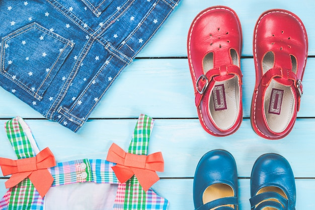 Zubehör des kleinen mädchens. buntes kleid, schuhe und jeans auf blauer pastellholzoberfläche.