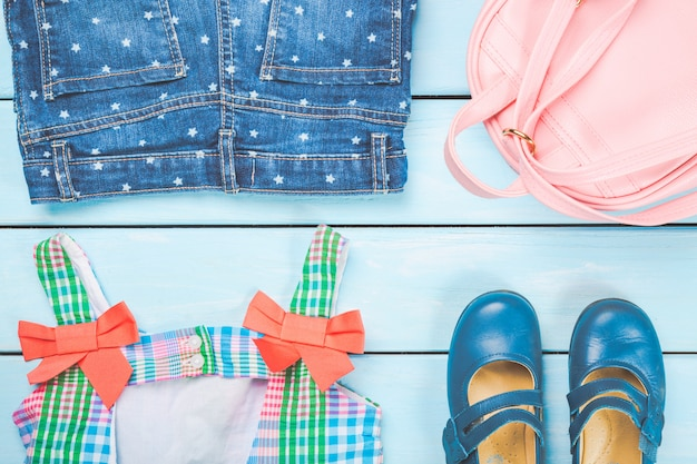 Zubehör des kleinen mädchens. rosa tasche mit buntem kleid, schuhen und jeans auf blauer pastellholzoberfläche.