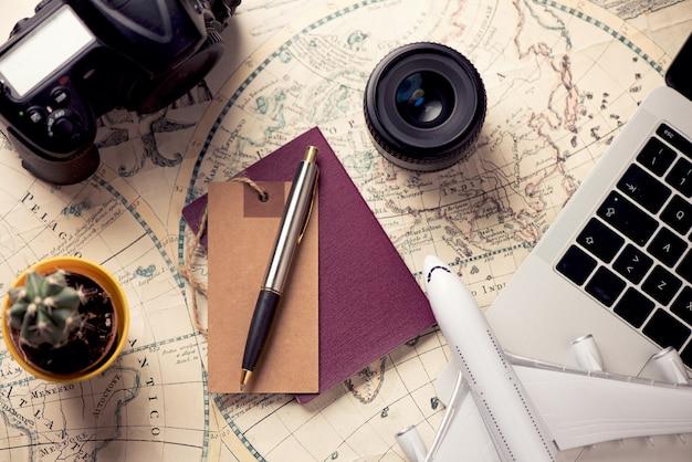 Zubehör für die reise. reisepass, fotokamera, smartphone und reisekarte. ansicht von oben. ferien- und tourismuskonzept
