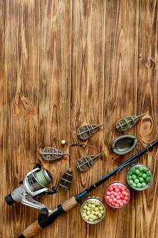 Zubehör für karpfenangeln und fischköder auf holzbrettern mit kopierraum.