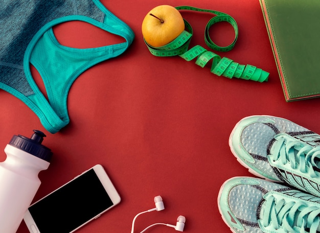 Zubehör für sport auf rotem hintergrund legen draufsicht. fitness, gesunde und aktive lebensweise.