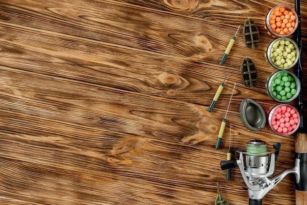 Zubehör zum karpfenangeln und angelköder auf holzbohlen mit kopierraum.