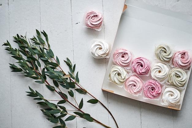 Zubereitete baiser oder marshmallows oder cupcakes in konditorei auf weißem tisch