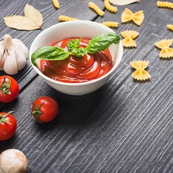 Zubereitete frische tomatensauce mit basilikumblatt auf tabelle