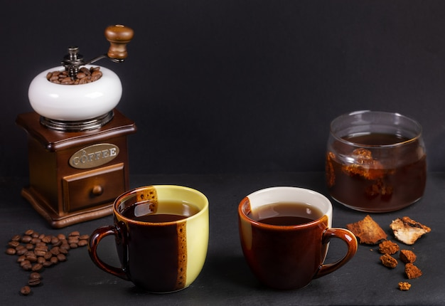 Zubereitung chaga pilze kaffee. zwei zweifarbige keramikbecher, glas mit chaga-getränk, kaffeemühle auf schwarz.