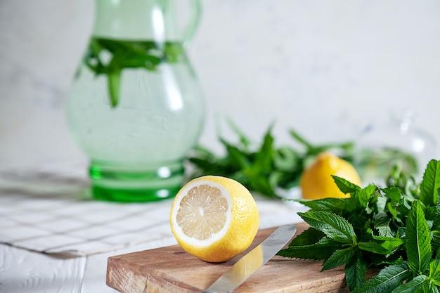 Zubereitung des limonadengetränks. geschnittene zitrone an bord mit frischer minze. erfrischendes, kaltes sommergetränk. limonadenkrug. herstellung traditioneller, gesunder limonade. zutaten für die herstellung von mojito