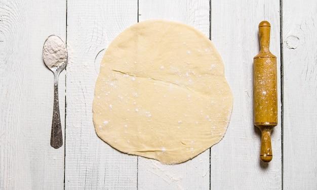 Zubereitung des teigs. der ausgerollte teig mit einem nudelholz und einem löffel mehl. auf einem weißen hölzernen hintergrund. freier platz für text. draufsicht