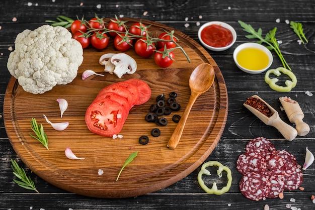 Zubereitung des teigs und gemüses zur herstellung von pizza. zutaten für die herstellung von pizza auf einem hölzernen hintergrund