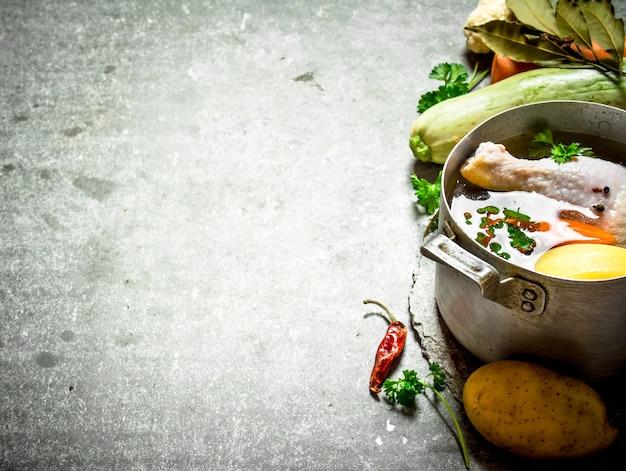 Zubereitung einer duftenden hühnersuppe mit frischem gemüse. auf dem steintisch.