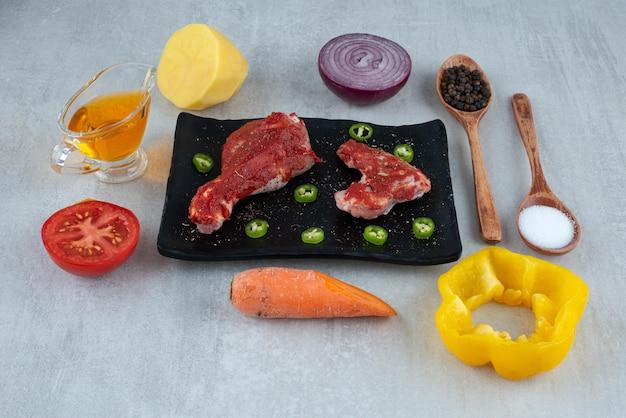 Zubereitung für hühnchen mit öl, gewürzen und gemüse.