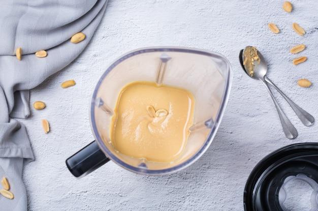 Zubereitung glatte hausgemachte erdnussbutter in einem mixer, mixer, küchenmaschine. ansicht von oben, flacher hintergrund