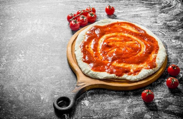 Zubereitung pizza. teig auf einem schneidebrett mit kirschtomaten. auf rustikalem hintergrund
