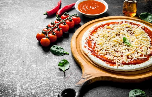 Zubereitung pizza. teig mit tomatenmark, käse und kirschtomaten auf rustikalem tisch ausrollen