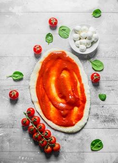 Zubereitung pizza. teig mit tomatenmark, mozzarella und spinat ausrollen. auf weißer holzoberfläche