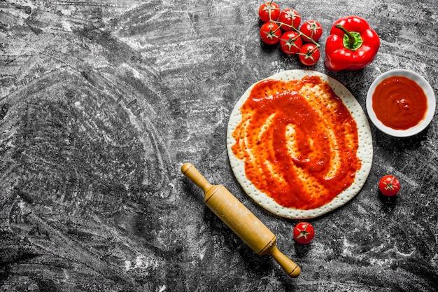 Zubereitung pizza. teig mit verschiedenen pizzabestandteilen ausgerollt. auf rustikalem hintergrund