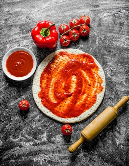 Zubereitung pizza. teig mit verschiedenen pizzabestandteilen ausgerollt. auf rustikaler oberfläche