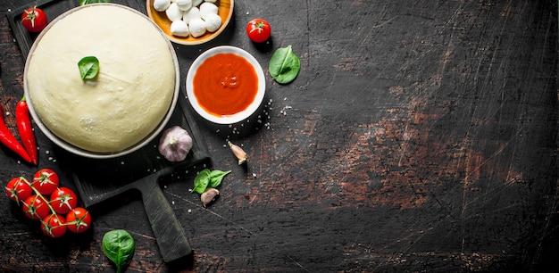 Zubereitung pizza. teig mit verschiedenen zutaten für pizza auf rustikalem tisch