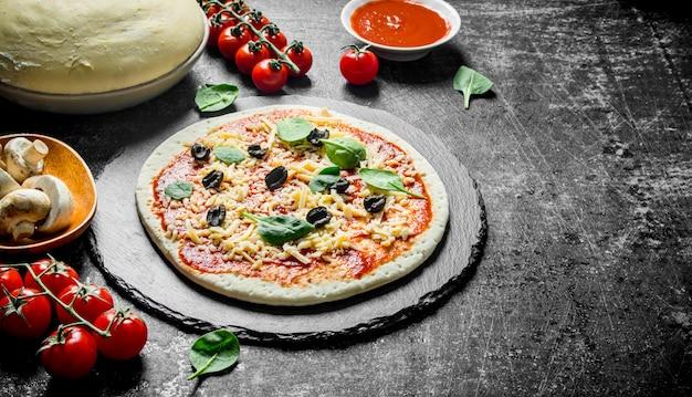 Zubereitung pizza. teig mit verschiedenen zutaten zum kochen von pizza. auf dunklem rustikalem hintergrund